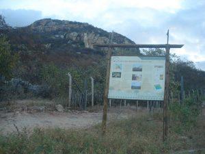Parte da Serra das Queimadas onde ocorre o Pegmatito Alto do Boqueirão, com um painel do Projeto Monumentos Geológicos sobre o pegmatito.